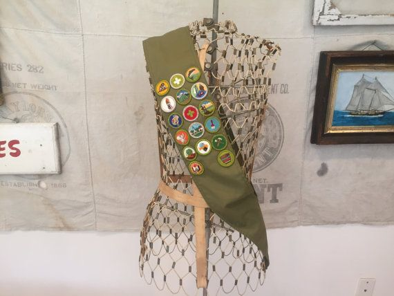 This is a vintage Boy Scout merit badge sash from the 1970s. It has 17 various merit badges sewn on a scout green sash. The badges are for many