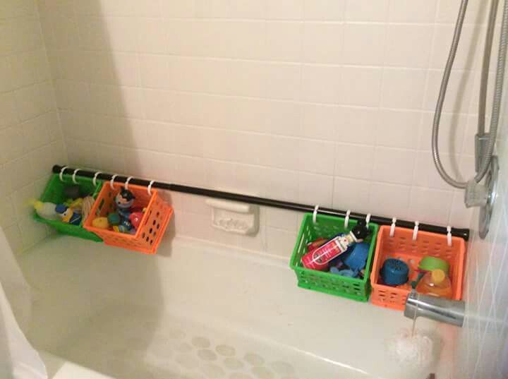 Use a shower curtain rod with hooks and baskets for kids bath toys :)