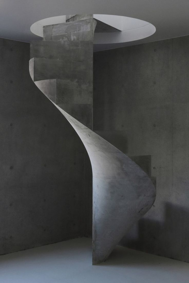 A tall guardless staircase made from cast concrete twists its way between bedrooms of this house located in the base of the structure and living spaces placed across the upper floor.