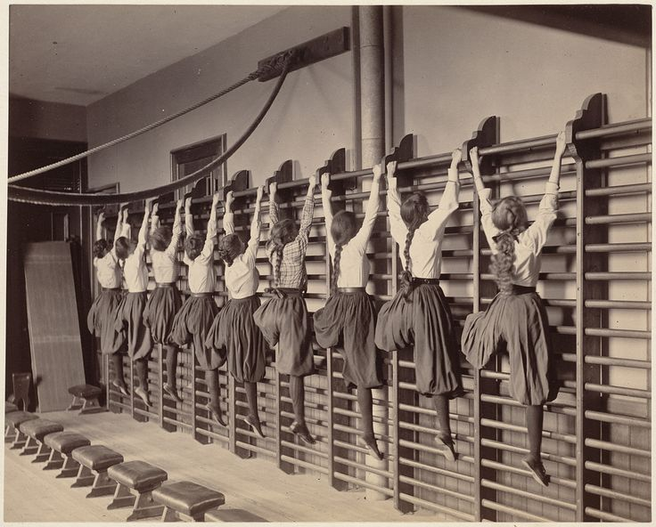 Girls exercising on bars against the wall, Charlestown High School, Boston, 1899