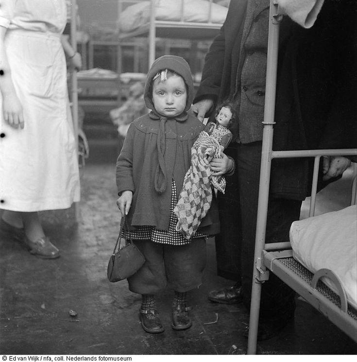 Geëvacueerd kind met pop in slaapzaal vlak na de watersnoodramp, Zeeland (1953)