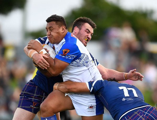Canberra Raiders Josh Papalii of Samoa is tackled by Luke Douglas and Frankie Mariano of Scotland of Scotland during the 2017 Rugby League World Cup match between Samoa and Scotland at Barlow Park on November 11, 2017 in Cairns, Australia.