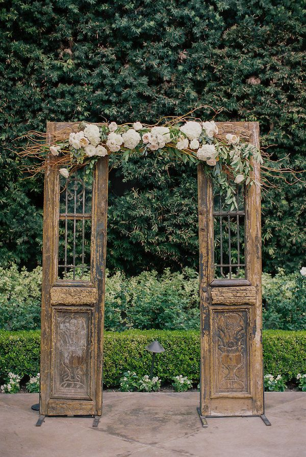 Small wooden doors with center florals for a ceremony backdrop