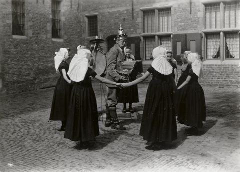 Straatmuzikant met een groep meisjes in Walcherse streekdracht. De meisjes zijn gekleed in zondagse dracht of uitgaanskleding. 1936 Middelburg vanAgtmaal
