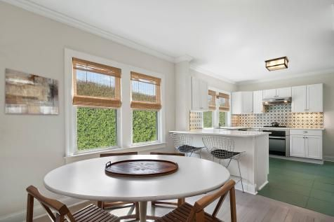 An+eclectic+mix+of+styles+adds+character+to+this+white+kitchen.+Wooden+dining+chairs+and+bamboo+Roman+shades+bring+warmth+and+natural,+textural+element.+Wire+bar+chairs+introduce+some+midcentury+modern+flair.