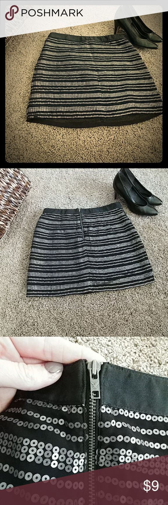AEO Mini Skirt Super cute and flashy layered mini skirt by American Eagle. In EXCELLENT condition. No issues at all. Silver sequins cover the skirt, front and back. Zipper in the back is a gray metal stamped with AE emblem.  This is a perfect piece for a girl's night out or a date night with your ??!!  Total length is 16 in. Thanks!! American Eagle Outfitters Skirts