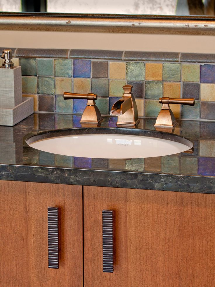 The brushed bronze fixtures in this southwest-style bathroom balance the color and texture of surrounding elements. A mosaic tile backsplash picks up the warm hues in the wood cabinets and grays in the countertop.
