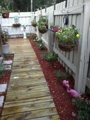 We have a very small backyard. Theres more sand than dirt, so after 2 years of trying to get grass to grow....this was our solution. My hubby build a boardwalk from the gate towards the more open area of the yard. The boardwalk expanded into a deck area. We planted miniature rose bushes and mini gardinias along the fence, then used red mulch for ground cover. Hanging baskets with colorful flowers were added, as well as a few shelves with pots of flowers. Its very qaint and