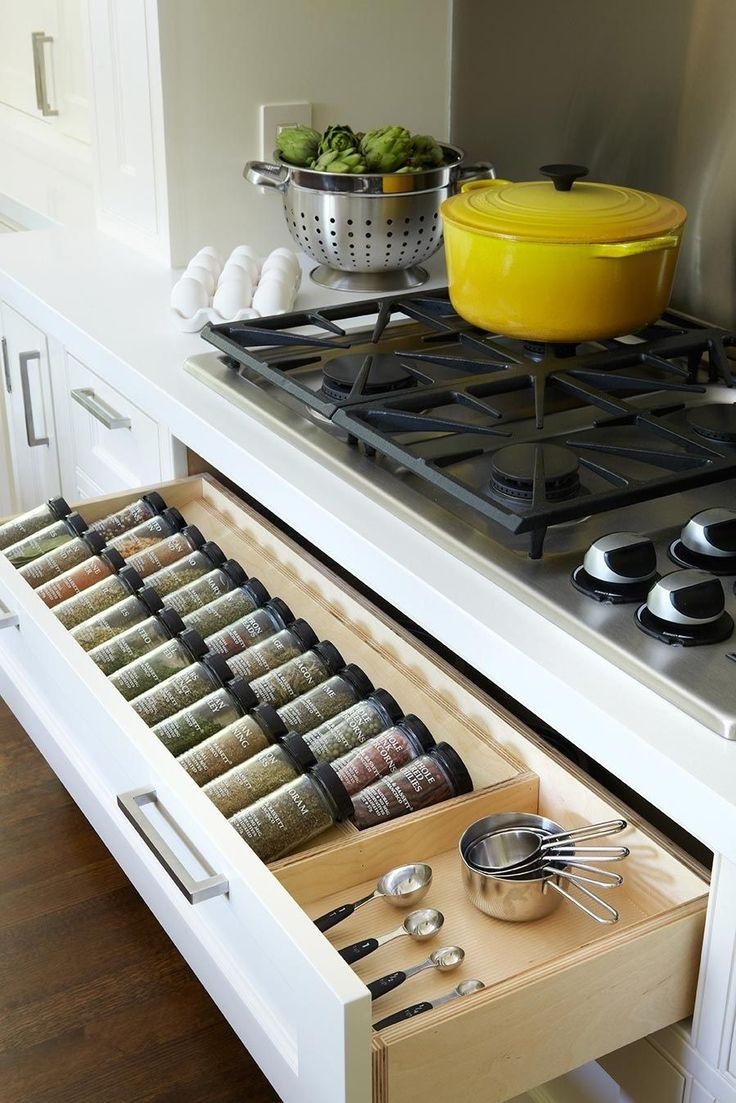 Maximize kitchen convenience with a narrow drawer beneath the range filled with neatly organized spices, measuring cups, and spoons.