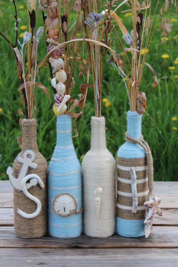"These bottles are wrapped with various colored yarns and twine and spell out the word ""Sail."" Each letter is created using nautical themed items."