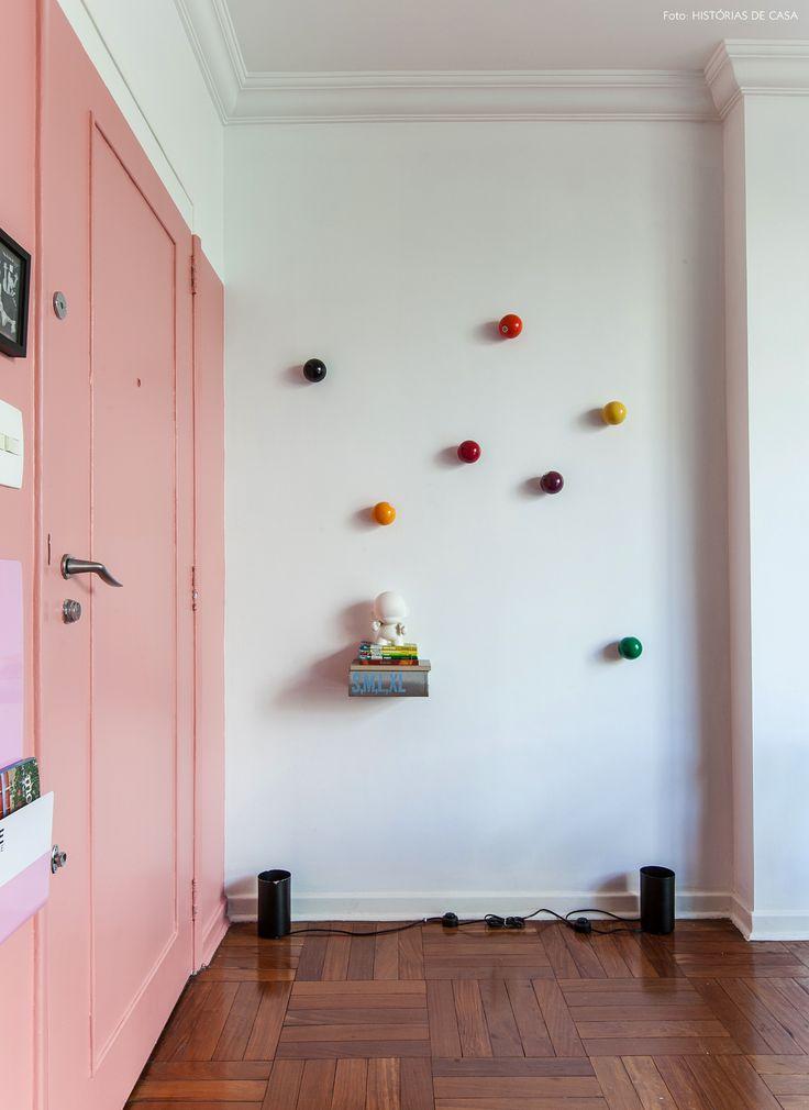Sala de jantar tem parede pintada de rosa e ganchos de parede que simulam bola de bilhar.