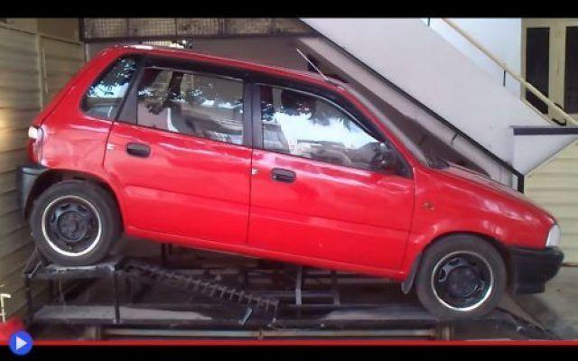 """L'espediente del garage grande come un armadio """"No, no. Non può riuscirci. Cara, prendi la telecamera! C'è un uomo che sta per impegnarsi nel più arduo ed improbabile dei parcheggi. La vedi la Suzuki Maruti Zen rossa? Vuole metterla là dentro. LÀ #auto #divertente #garage #guida #india"""