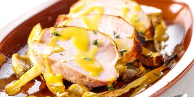 In de oven gebraden beenham op een bedje van met honing gekaramellisseerde pastinaken, aardappelen en sjalotjes.