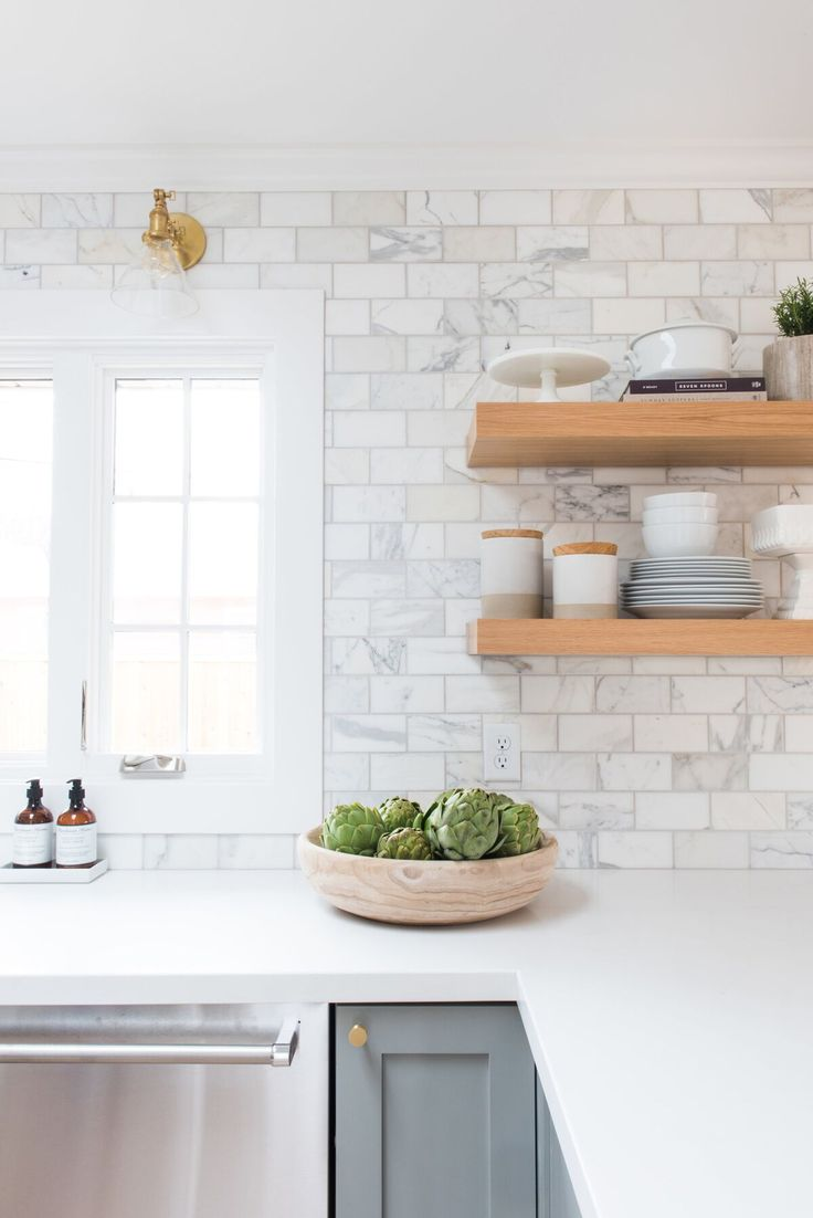 pale grey cabinets, marble subway tile, brass sconces, floating shelves in wood