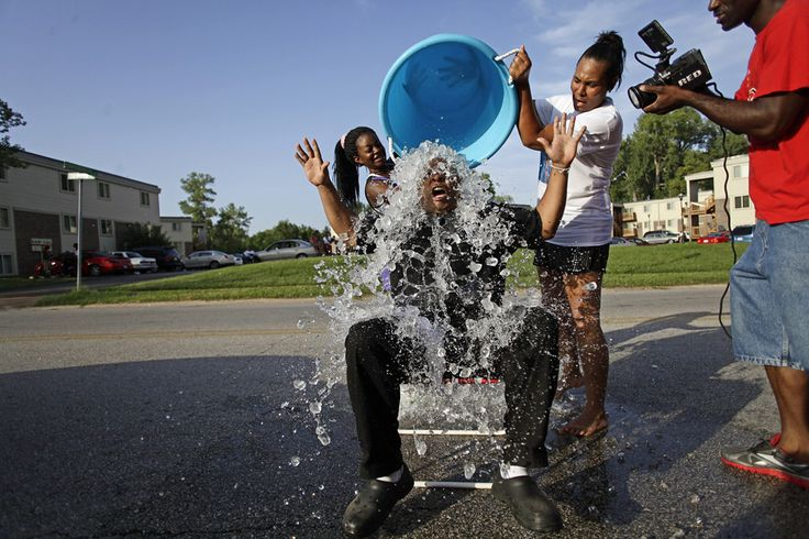 Kalisha Gilmore (L) and Recorida Kennedy (2nd R), pour ice water on Kevin Ephron as he takes the ice bucket challenge in remembrance of Michael Brown along Canfield Drive, where he was fatally shot by a police officer in Ferguson, Missouri August 24, 2014. REUTERS/Joshua Lott