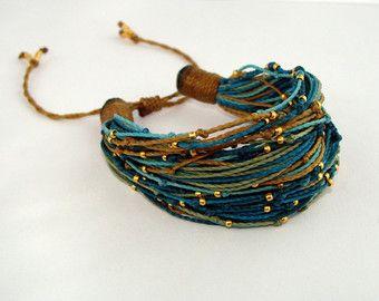 Esta pulsera chic boho está hecha de cuerda de poliéster encerado, decorado con pequeños granos de oro. Pulsera hecha a mano es fácil de ajustar tirando de