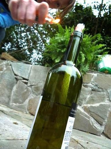 DIY tiki torch wine bottles for Under $4.00 that look pretty and keep the mosquitoes away.