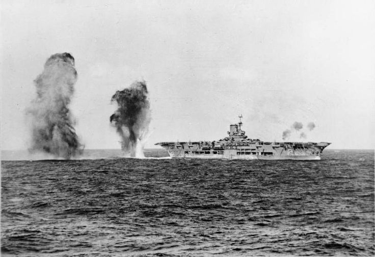 Bombs falling astern of HMS Ark Royal (91) during an attack by Italian aircraft during the Battle of Cape Spartivento The photograph was taken from the cruiser HMS Sheffield (C24),	27 November 1940