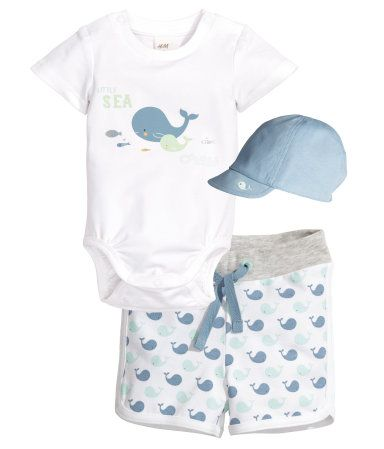 CONSCIOUS. Three-part set in organic cotton jersey. Short-sleeved top with printed design at front. Patterned shorts with elasticized waistband. Soft, lined hat.