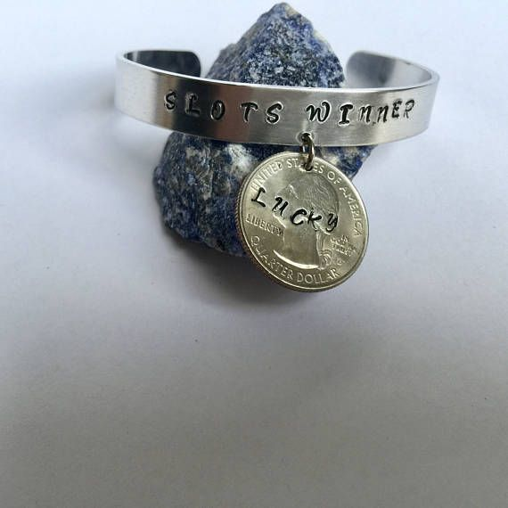 Wear a lucky quarter next time you head to the casino! Hand-stamped SLOTS WINNER on 3/8 aluminum cuff. A hand-stamped LUCKY quarter is attached as a charm! Great item for the slots player in your life - nothing beats good luck.
