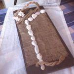 Χειροποίητος δίσκος σε καφέ στα χερούλια καραβόσκοινο πλαισιωμένο μα λινάτσα λεύκες πέτρες υαλοξυλα και κοχύλια
