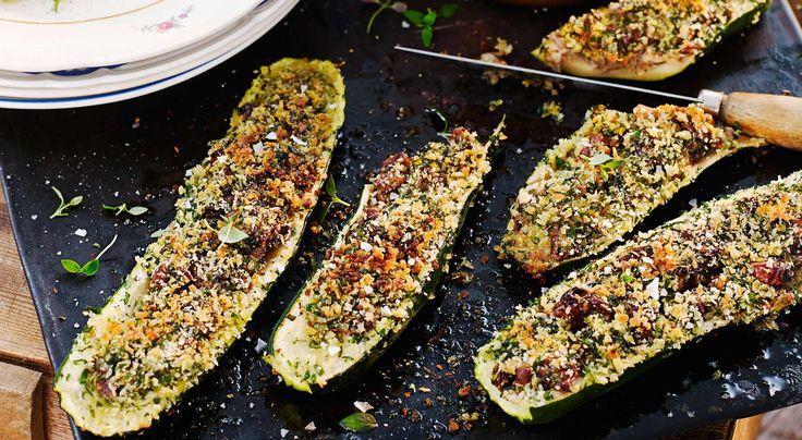 Recept på bakad zucchini fylld med valnötter, russin och örter. Smaksätt gärna tomatsåsen med lite strimlad basilika. Den som önskar en matigare måltid kan lägga till bröd, potatis eller matvetesallad.