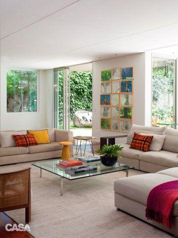 Carioca radicada em São Paulo, a proprietária adotou em sua morada a descontração típica da terra natal. Mesa lateral, banco amarelo e almofadas da Conceito Firma Casa.