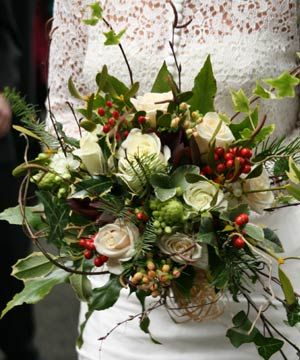 the winter theme of ivy, holly, foliage, hypericum berries and twigs was offset with two roses 'avalanche' and 'champagne', with ornithogalum (black-eyed Susie) all loosely tied with raffia.