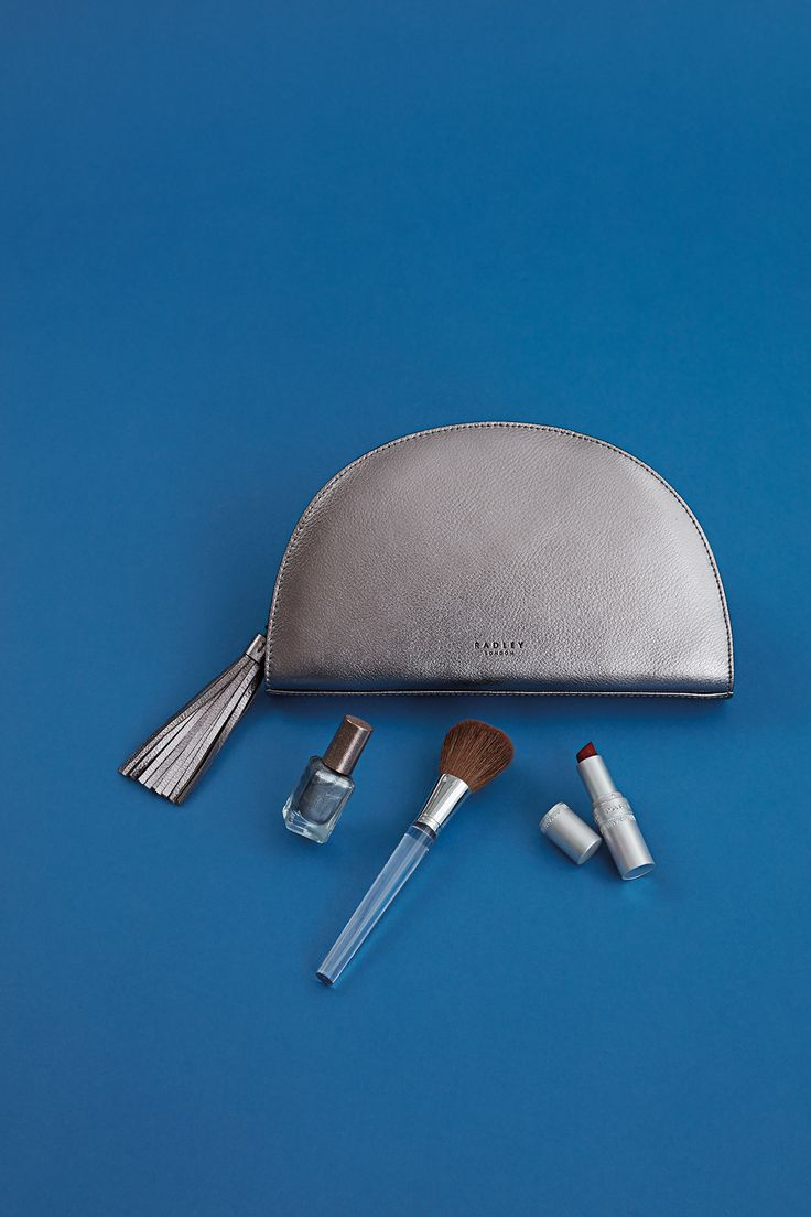 Shine bright with a silver style! This sophisticated half-moon shape clutch bag is crafted from smooth leather and features a playful tassel charm.