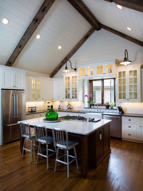 Design ideas for a mid-sized country open plan kitchen in Atlanta with glass-front cabinets, white cabinets, stainless steel appliances, white splashback, subway tile splashback, dark hardwood floors and an island.