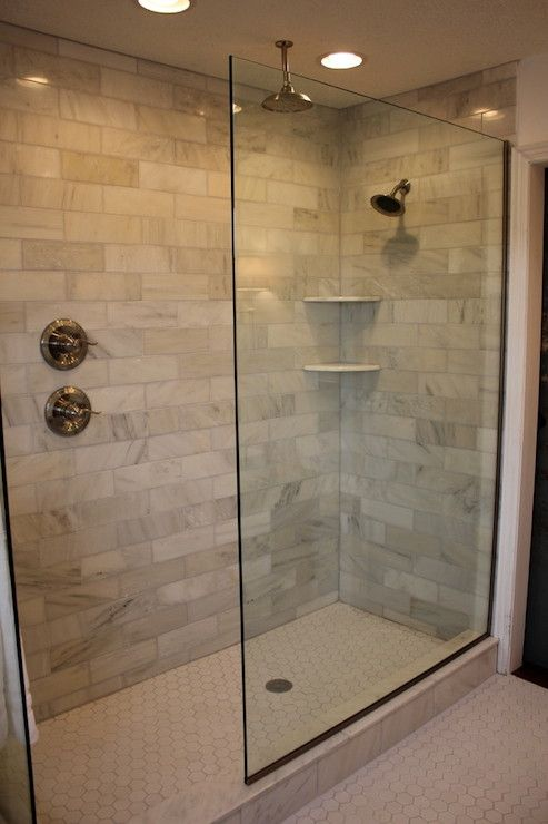 the doorless glass showerdoorless glass shower marble subway tile rain head and shower head added recessed lighting and a new hexagon white tile floor