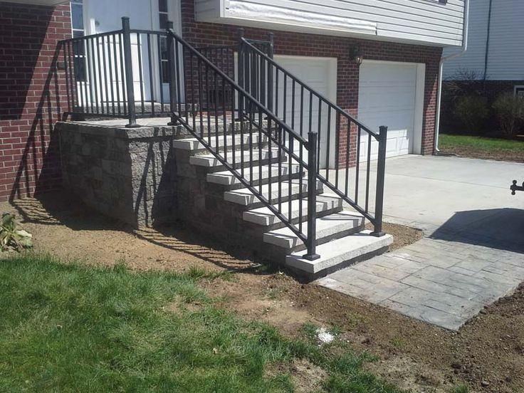 Front porch done in Versa-Lok wall stone, limestone slab steps, aluminum railings, and paver stone landings.