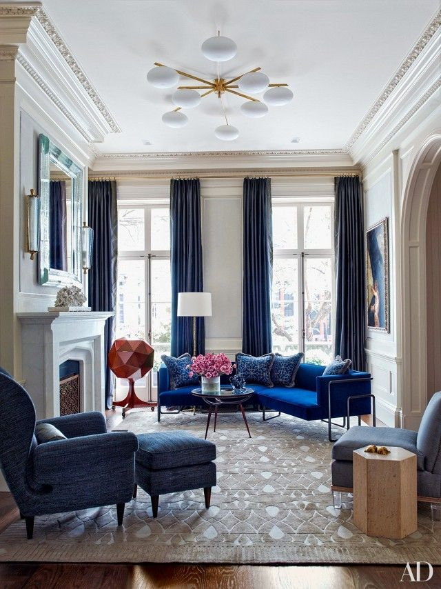 Small living room with blue #velvet upholstery, tall #window panels and a modern ceiling #light fixture