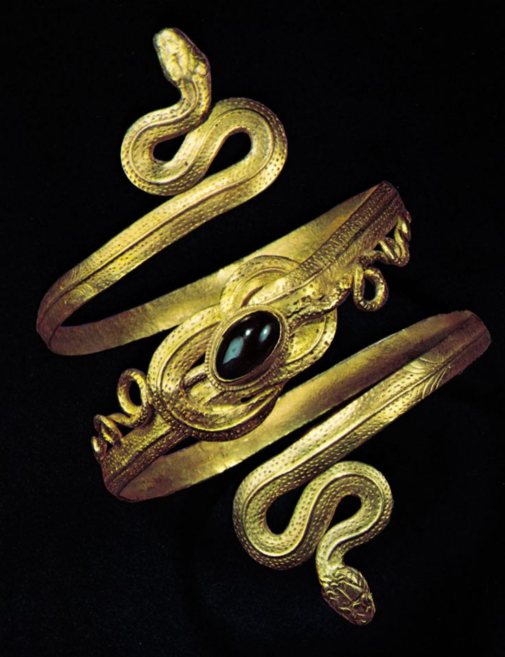 Greek gold spiral bracelet of two snakes whose tails are tied in a Hercules knot that is decorated with a garnet in a bezel setting; in the Schmuckmuseum Pforzheim, Germany.