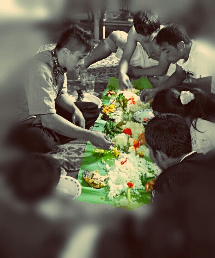 Padang, West Sumatera, Indonesia. Family eat together with a huge single banana leaf as a plate.