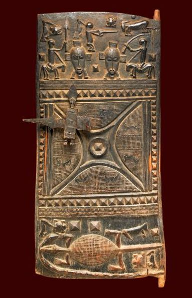 Africa | Door. Senufo peoples.  Ivory Coast | ca. 1920s | Wood and iron | Wealthy and powerful individuals in the northern Senufo region commissioned intricately carved doors as symbols of prestige. This door is similar to others carved in the 1920s in Boundiali by the sculptor Yalokone and his workshop