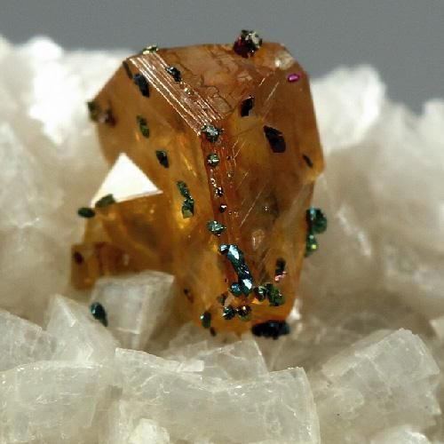 :A cute thumbnail showing a honey coloured twinned crystal of sphalerite overgrown by multicoloured chalcopyrite on a matrix of snowy white dolomite.
