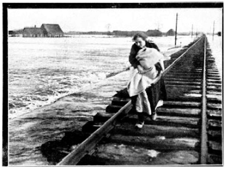 Een vrouw brengt haar kind in veiligheid over de spoorbaan in Wijchen, de enige verbindingsweg die nog te gebruiken is tijdens de watersnoodramp van 1926.