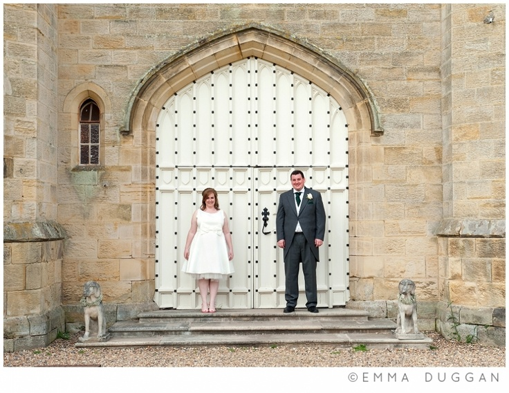 Bride & groom in front of the South Doors at Chiddingstone Castle with stone dogs