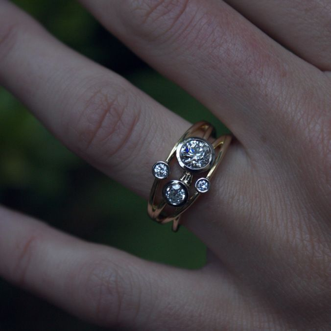 18ct gold and platinum crossover cocktail ring with diamonds. The largest diamond is a family heirloom so I used this as the centrepiece in the design. The other diamonds create a wash of sparkle - all set in 18ct yellow gold on criss-crossing bands.