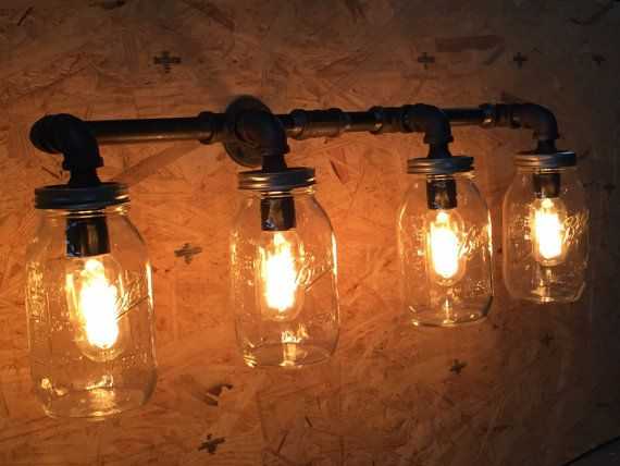 Handmade industrial style farmhouse light. Made with ALL brand new parts, including all UL parts. This is made with 100% black iron pipe, very sturdy and will withstand the test of time. Mason jars used are wide-mouth quart jars that you can put nearly any sort of shape/size light bulb into. These look particularly stunning with edison-style light bulbs. They work perfectly over a bathroom vanity or a kitchen sink. Can also be made into a hanging fixture for your farmhouse table.  Also f...