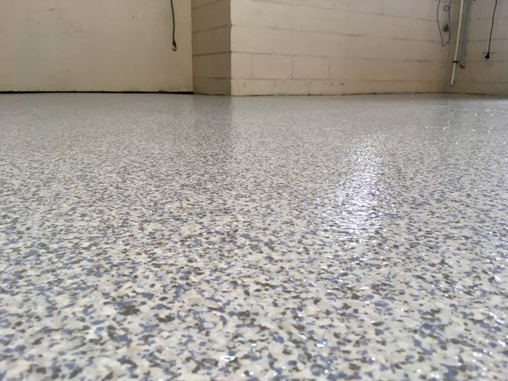 'Frozen' epoxy flake over a white base coat by The Garage Floor Co. looks amazing on any concrete floor.