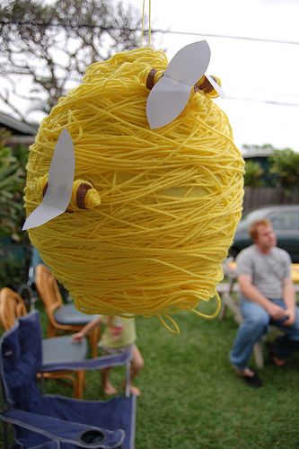 """Bee Pinata... Wrap a round pinata in yellow yarn and display a few bees on the """"hive""""... if you don't want to do a pinata, then you could cover balloons or styrofoam or something of the shape and hang around as decor."""