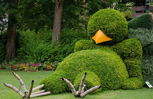 Sleepy Chick - Le Jardin des Plantes - large topiary in the shape of a sleeping bird with a green bulbous belly, bright yellow beak, and bamboo feet. Poussin Endormi, or Sleepy Chick, is part of children's literature author and illustrator Claude Ponti's second topiary exhibition in the oldest and largest botanical garden in Nantes, France. Just too cute!