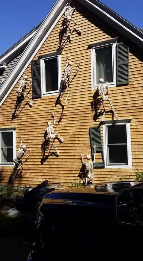 halloween decorations with skeletons climbing up the side