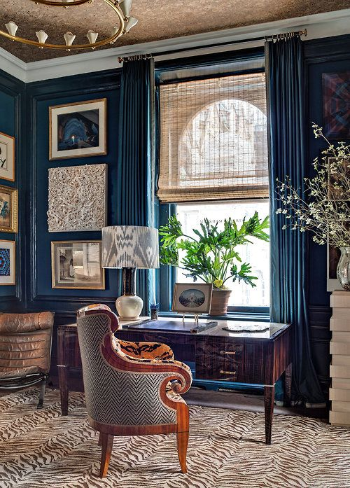 Deep blue study filled with art. Love the chair fabric, roman shade and rug.