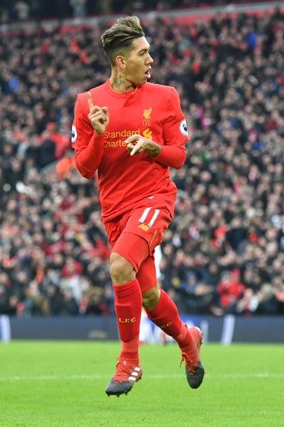 Liverpool's Brazilian midfielder Roberto Firmino celebrates scoring their second goal to equalise 2-2 during the English Premier League football match between Liverpool and Swansea City at Anfield in Liverpool, north west England on January 21, 2017. / AFP / Anthony DEVLIN / RESTRICTED TO EDITORIAL USE. No use with unauthorized audio, video, data, fixture lists, club/league logos or 'live' services. Online in-match use limited to 75 images, no video emulation. No use in betting, games or…