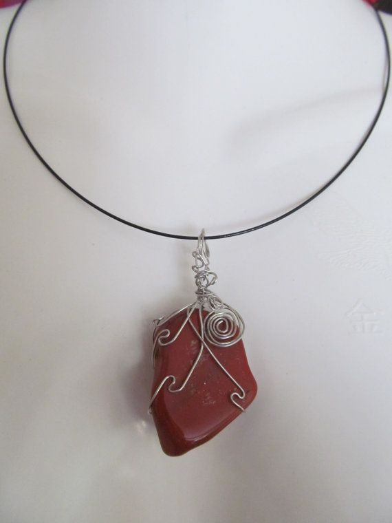 The color of the red Kalahari dunes captured in a semi precious red Jasper stone. Free form wire wrapping, mounted on a black beading ring.