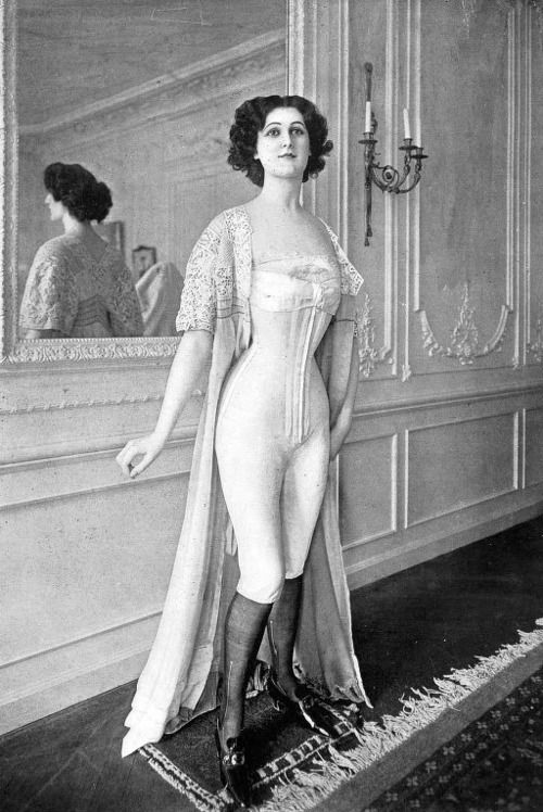 Model at a Belle Epoque couture house before donning her gown. (Models wore special sheath like undergarments to protect the gowns). Possibly a model at Margaine Lacroix wearing one of the designers elasticized corset/combination combinations.