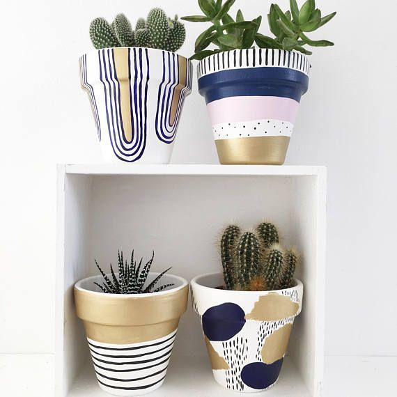 A hand painted plant pot with deco-esque deep blue and gold design. A very fine …